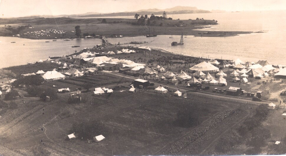 Evening Post* Photo. SCENE OF TODAY'S BIG HUI AT WAITANGW general view of the encampment at Waitangi, where the -Treaty, celebrations commence-today. In the right background^ amidst the trees, is the Treaty House,^surrounded by the land which' goes vJiili^ the' Governor-Generals gift to the nation. In the centre of: the picture, to the right of the. road, is the area setassideforthe celebrations: The steam ?: and smoke on the left indicate the position of the'cooking pots'. (Evening Post, 05 February 1934). Alexander Turnbull Library, Wellington, New Zealand. http://natlib.govt.nz/records/19199051