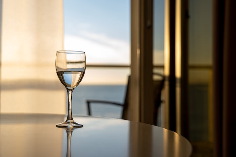 Glass of wine with sea view at Whangaparaoa Lodge for a romantic getaway in Auckland